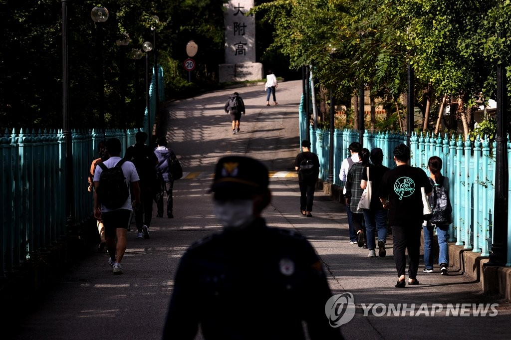 Test-takers walk in two lines to comply with social distancing guidelines before entering a venue for an exam for public servants in western Seoul on Sept. 26, 2020. (Yonhap)
