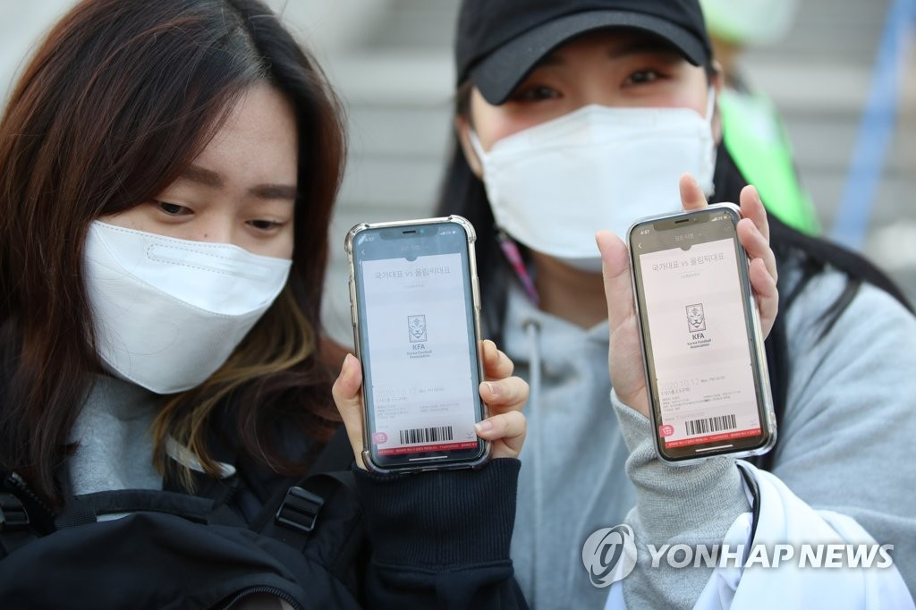 Fans hold up mobile tickets before entering a soccer event in Goyang, north of Seoul, on Oct. 12, 2020. (Yonhap)