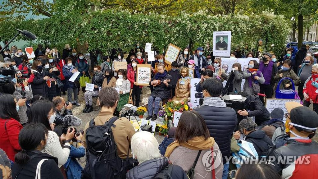 Activists and citizens hold a rally in front of the Statue of Peace near Mitte district office in Berlin on Oct. 13, 2020, calling for the withdrawal of the district office's order to remove the Statue of Peace, which symbolizes Korean victims of Japan's wartime sexual slavery. (Yonhap)