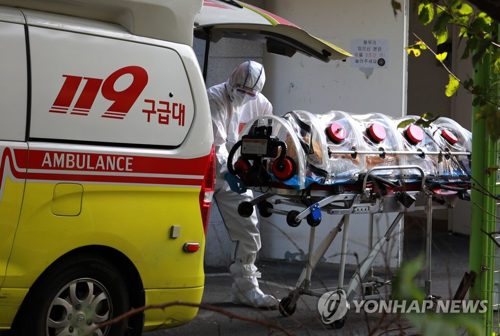 A patient is loaded into an ambulance at Haeddeurak Hospital in the southern city of Busan on Oct. 14, 2020, after dozens of patients and workers at the senior-care facility were diagnosed with COVID-19. (Yonhap)