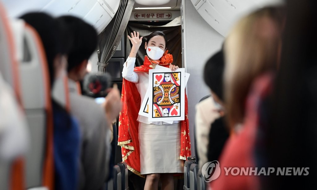This photo, provided by the Incheon International Airport press pool, shows a flight attendant performing magic aboard a Jeju Air flight to nowhere on Oct. 23, 2020. (Yonhap)