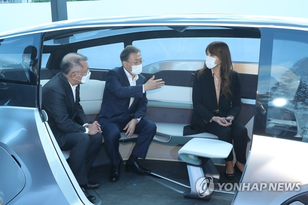President Moon Jae-in (C) rides the concept autonomous vehicle M.Vision S of Hyundai Motor Co., at the automaker's plan in Ulsan, 415 kilometers southeast of Seoul, on Oct. 30, 2020. Moon visited the plant as part of a series of tours of key sectors of the government's New Deal initiative, accompanied by Hyundai Motor Group chief Chung Euisun (L). (Yonhap)