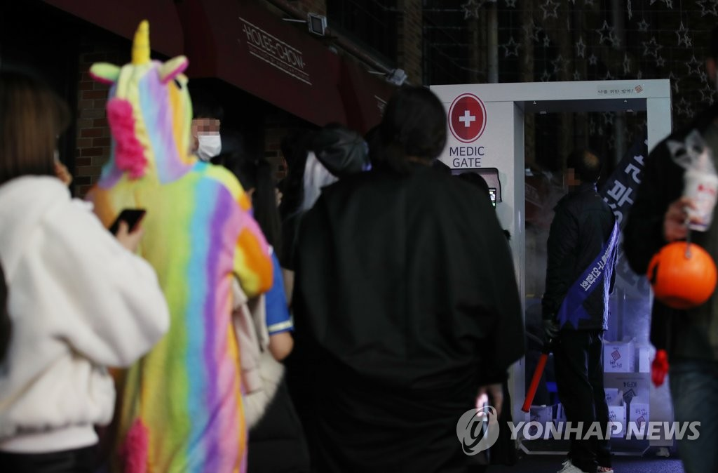 Citizens enjoying Halloween pass by a medic gate installed in Itaewon, central Seoul, to prevent the spread of new coronavirus infections on Oct. 31, 2020. (Yonhap)