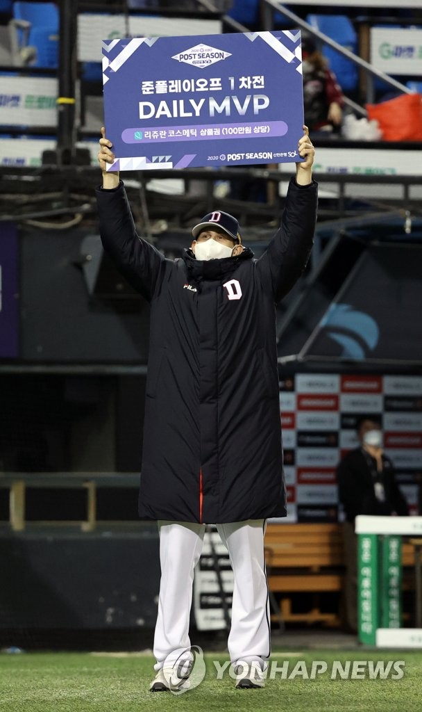 Chris Flexen of the Doosan Bears hoists the sign showing him as the Player of the Game for Game 1 of the Korea Baseball Organization first-round playoff series against the LG Twins at Jamsil Baseball Stadium in Seoul on Nov. 4, 2020. (Yonhap)