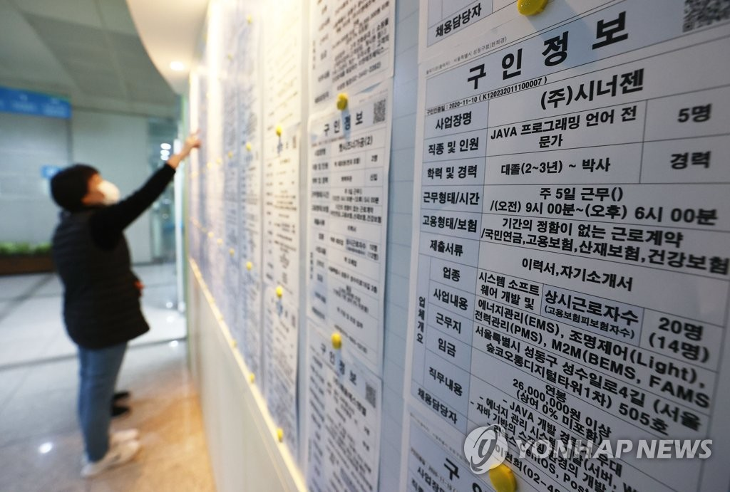 The file photo taken on Nov. 11, 2020, shows a citizen looking at job information at an employment arrangement center in Seoul. (Yonhap)
