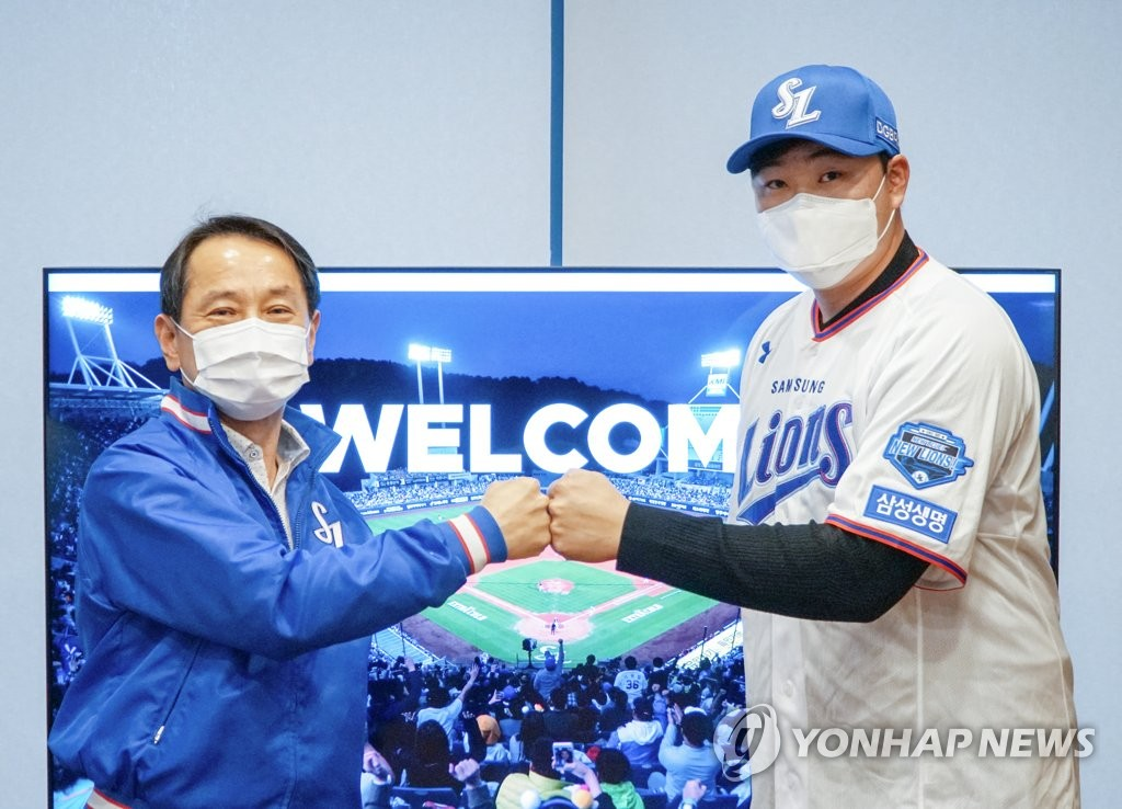 In this Dec. 14, 2020, file photo provided by the Samsung Lions, Oh Jae-il (R), new first baseman for the Korea Baseball Organization club, bumps fists with the Lions CEO Won Gee-chan after signing a four-year contract. (PHOTO NOT FOR SALE) (Yonhap)
