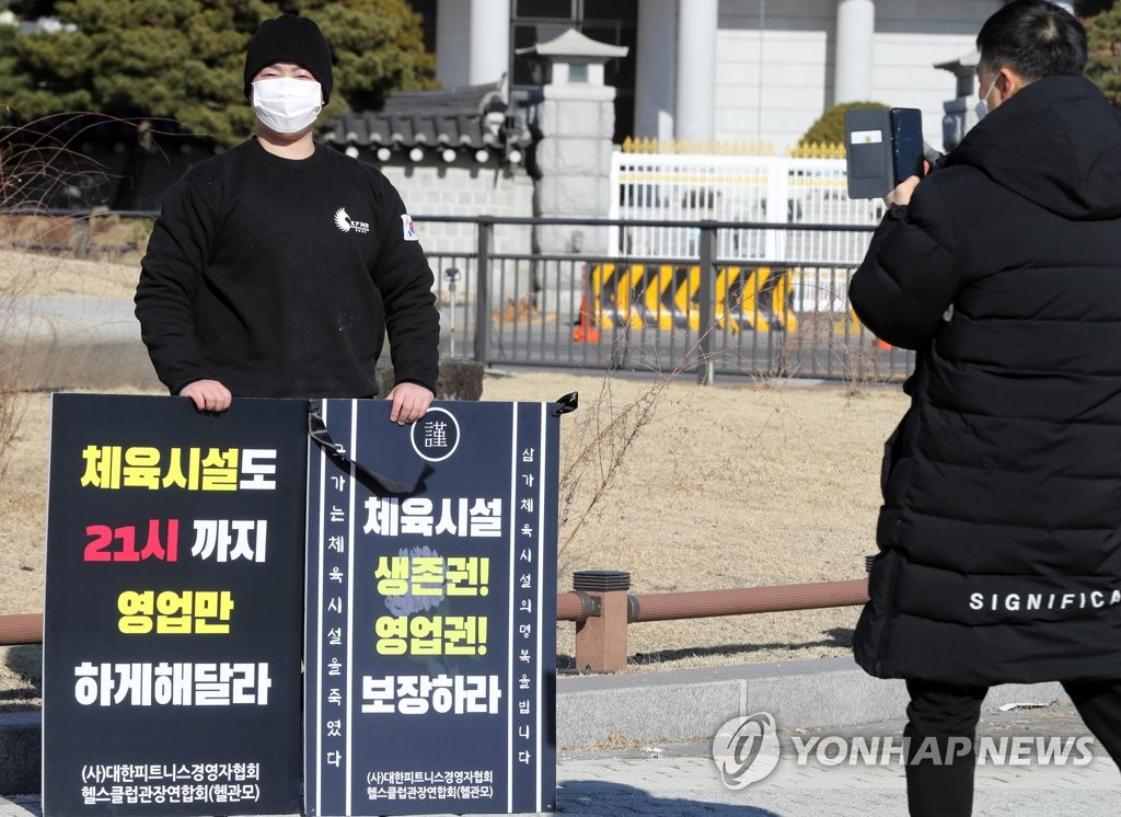 In this file photo, a member of the Korea Fitness Manager Association stages a one-person protest against the government's coronavirus restrictions in front of Cheong Wa Dae on Dec. 20, 2020, demanding sports facilities be allowed to run until 9 p.m. like other facilities including restaurants and cafes. (Yonhap)