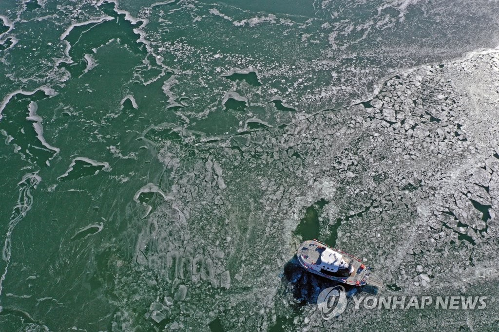 A ferry makes its way through the ice-covered Bukhan River in the city of Chuncheon, Gangwon Province, northeastern South Korea, on Jan. 8, 2021, to reach the river's tourist island of Nami, after the river froze following a cold snap that lowered the temperature in the region to an intraday low of minus 29.1 C. (Yonhap)