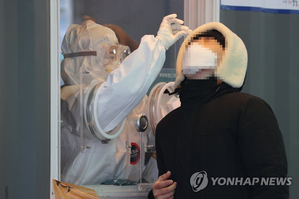 Medical workers carry out COVID-19 tests at a makeshift clinic in central Seoul on Jan. 9, 2021. (Yonhap)