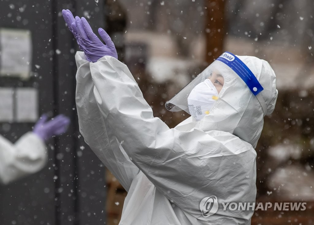 A health care worker enjoys the snow at a COVID-19 testing center set up at a parking lot in Yangcheon Ward, western Seoul, on Jan. 12, 2021. (Yonhap)
