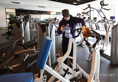 An employee at a gym in Yongin, south of Seoul, disinfects fitness equipment on Jan. 17, 2021, to prepare for opening as the government eases restrictions on indoor sports facilities. (Yonhap)