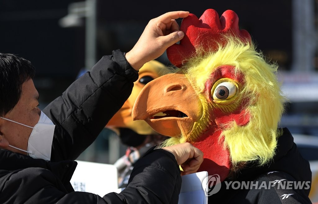 Protesters wearing masks stage a rally in central Seoul on Jan. 20, 2021, calling for the government to stop the culling of poultry potentially infected with avian influenza. (Yonhap)