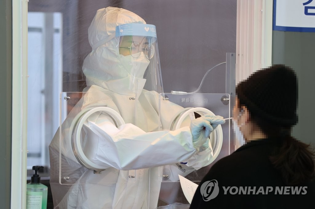 A health worker conducts a screening test at a temporary screening center set up in front of Seoul Station in central Seoul on Jan. 23, 2021. (Yonhap)