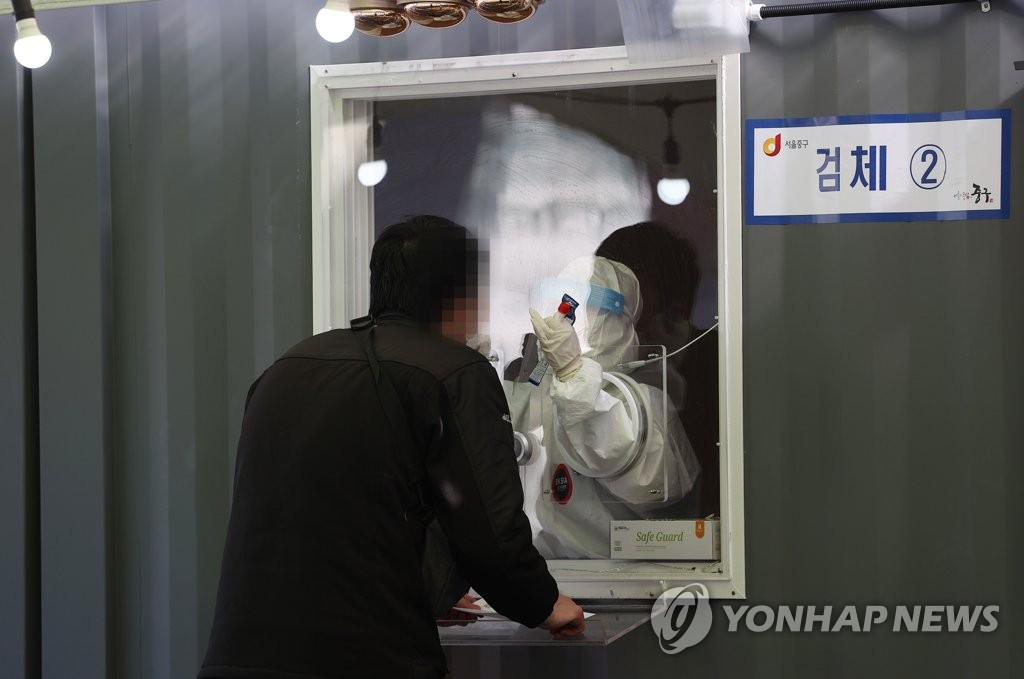 A medical worker collects a specimen for coronavirus testing at a temporary clinic in front of Seoul Station on Jan. 24, 2021, as the third wave of the COVID-19 pandemic, which started in November last year, shows signs of a let-up after peaking with daily cases of 1,241 on Dec. 25. (Yonhap)