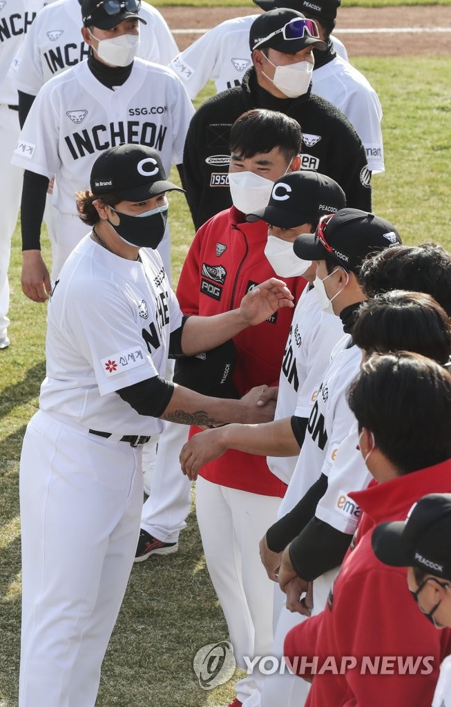 Choo Shin-soo of the SSG Landers (L) shakes hands with his teammates at Sajik Stadium in Busan, 450 kilometers southeast of Seoul, on March 11, 2021. (Yonhap)