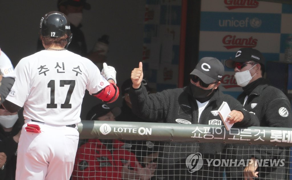 Choo Shin-soo of the SSG Landers (L) is greeted by his coaches after the end of the top of the third inning of a Korea Baseball Organization preseason game against the Lotte Giants at Sajik Stadium in Busan, 450 kilometers southeast of Seoul, on March 23, 2021. (Yonhap)