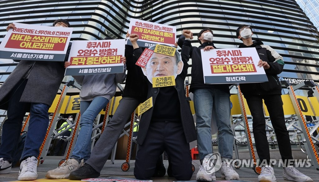 South Korean civic activists stage a protest against the Japanese government's decision to discharge radioactive water from the crippled Fukushima nuclear plant into the Pacific Ocean during a news conference in front of the Japanese Embassy in Seoul on April 13, 2021. (Yonhap)