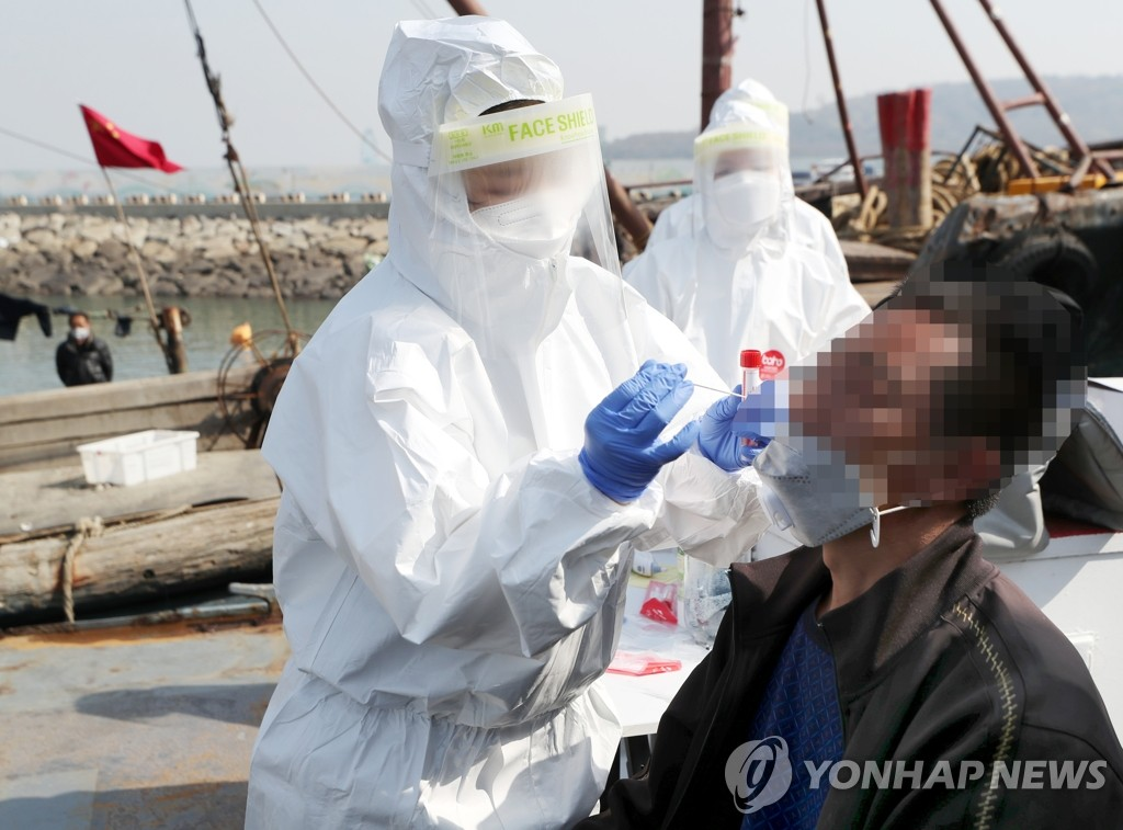 A health worker in a protective suit collects a sample from a Chinese sailor caught fishing illegally inside South Korean waters at a port in Incheon, 40 kilometers west of Seoul, on April 21, 2021. (Yonhap)