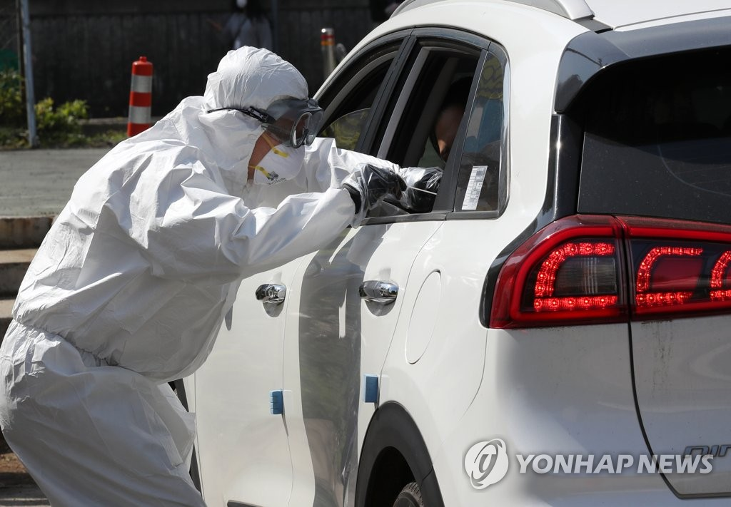 A health care worker conducts a COVID-19 test at a drive-through testing center in the southwestern city of Gwangju, 329 kilometers south of Seoul, on April 21, 2021. (Yonhap)