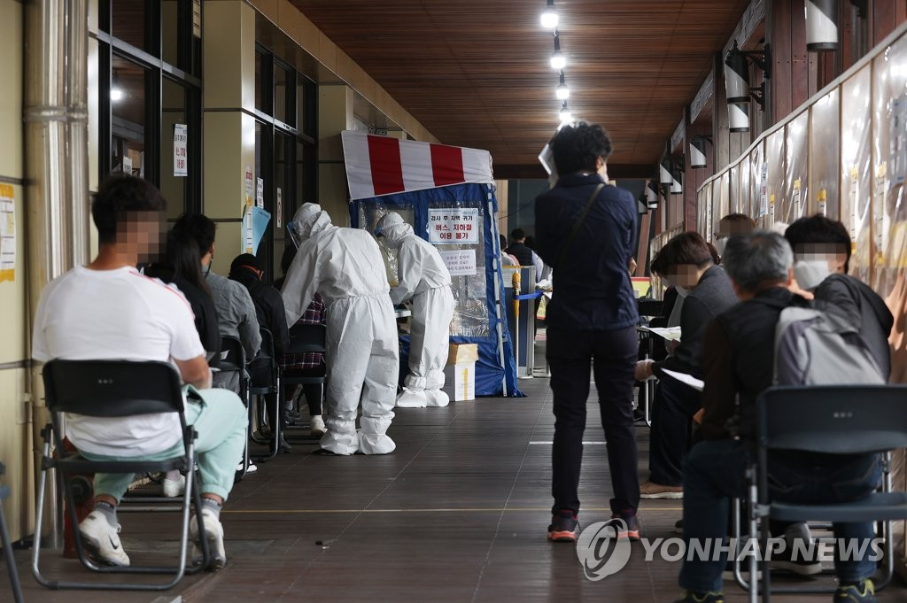 Citizens wait in line to receive COVID-19 tests at a makeshift virus testing clinic in Seoul on April 23, 2021. (Yonhap)