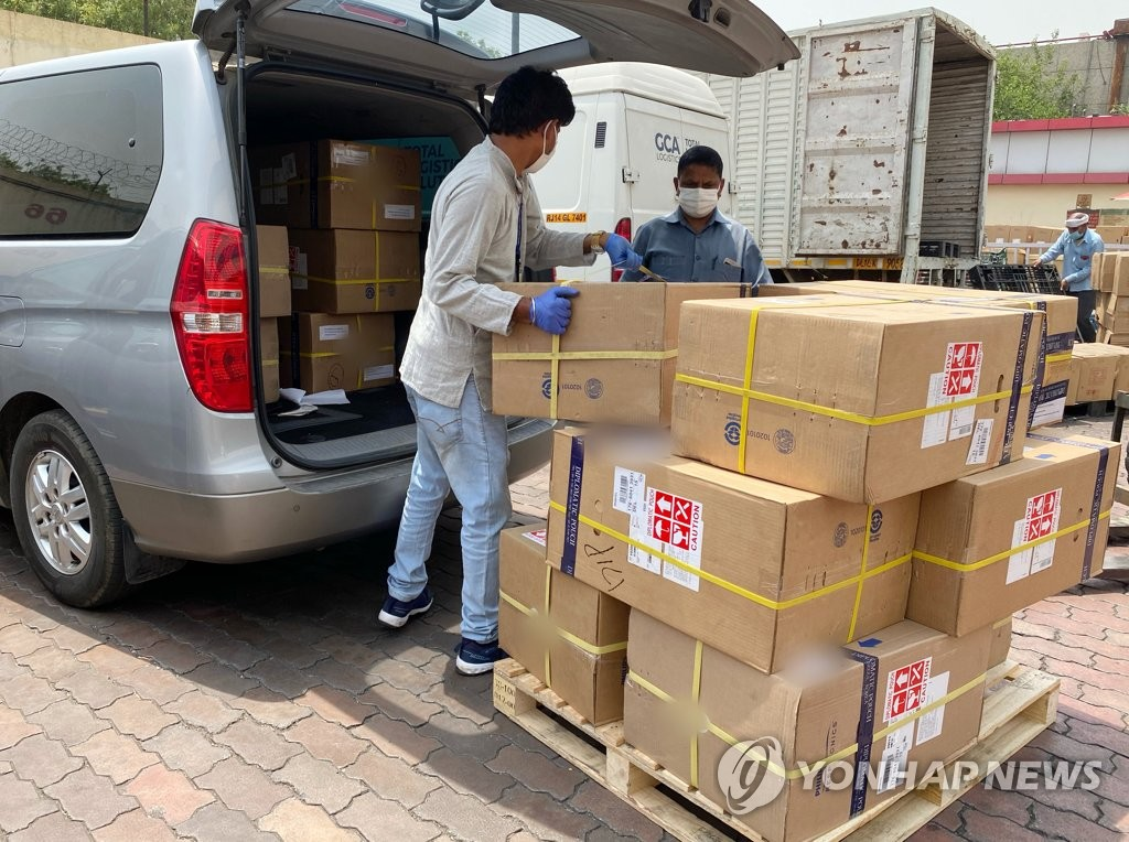 This photo, provided by the South Korean Embassy in India, shows workers moving 14 medical oxygen generators from South Korea that arrived in New Delhi on April 30, 2021, via a diplomatic pouch. (PHOTO NOT FOR SALE) (Yonhap)