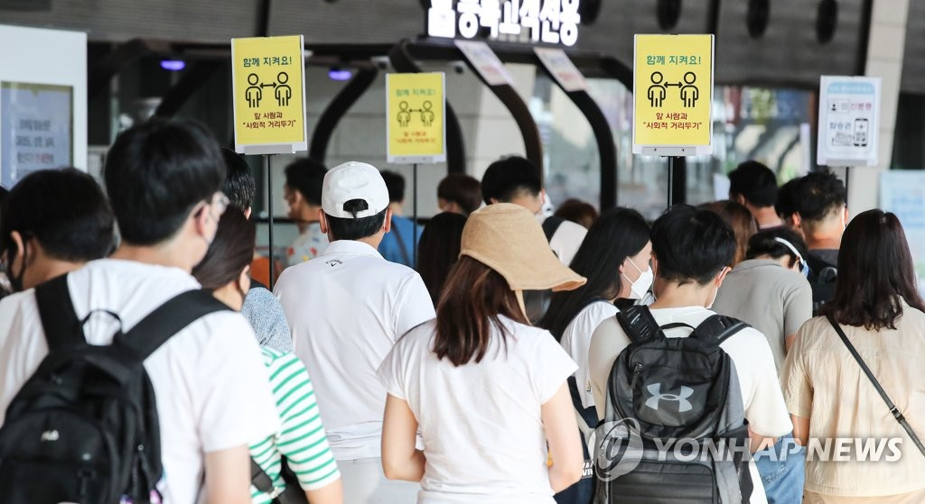 Travelers wait in line, with social distancing signs displayed in the background, at Gimpo International Airport in Seoul on July 30, 2021. (Yonhap)