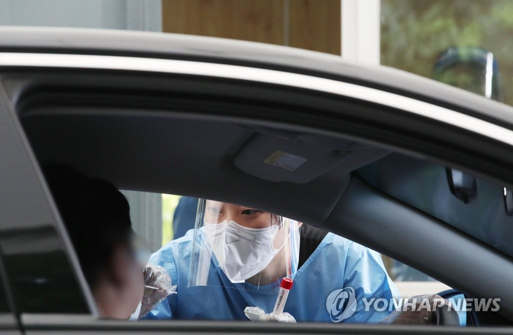 A medical worker takes a swab sample to test for COVID-19 at a drive-thru screening center in northern Seoul on Aug. 4, 2021. (Yonhap)