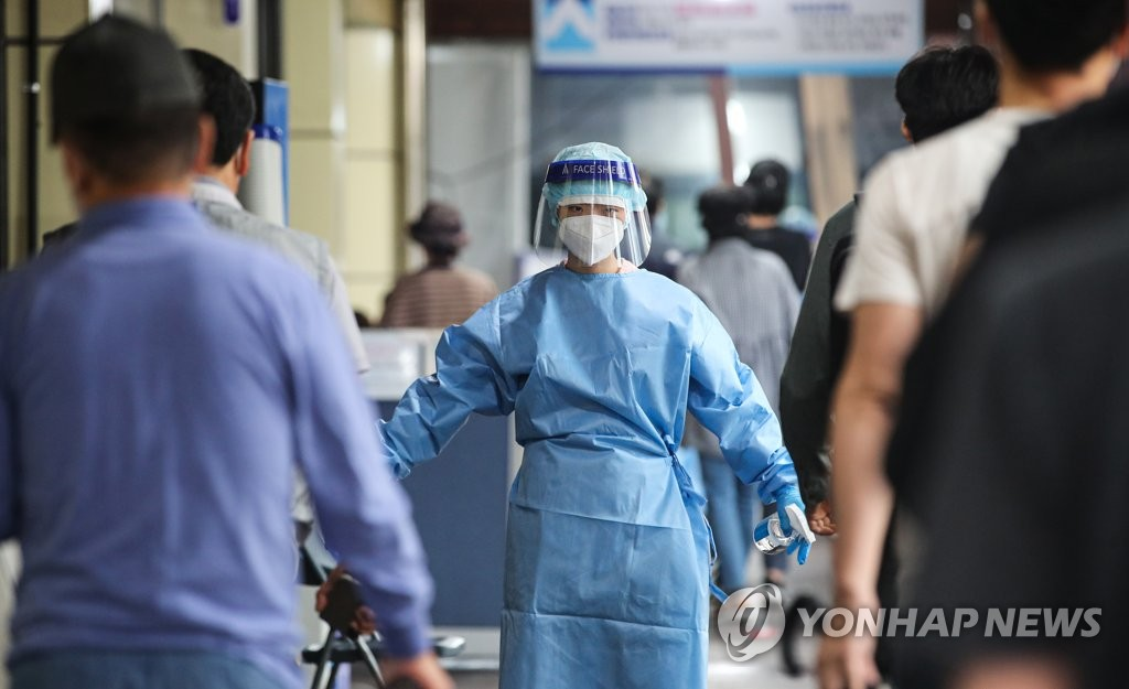 A medical worker wearing personal protective equipment guides people at a COVID-19 screening station in southern Seoul on Sept. 7, 2021. (Yonhap)