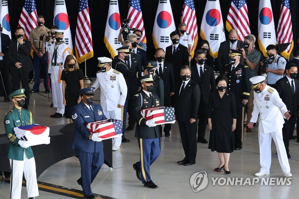 South Korean President Moon Jae-in (3rd from R), accompanied by Adm. John C. Aquilino (far R), commander of the U.S. Indo-Pacific Command, watches South Korean and U.S. honor guards carrying the remains of Korean and American troops killed during the 1950-53 Korean War during an alliance ceremony at Hickam Air Force Base in Honolulu, Hawaii, on Sept. 22, 2021, to transfer the remains. (Yonhap)